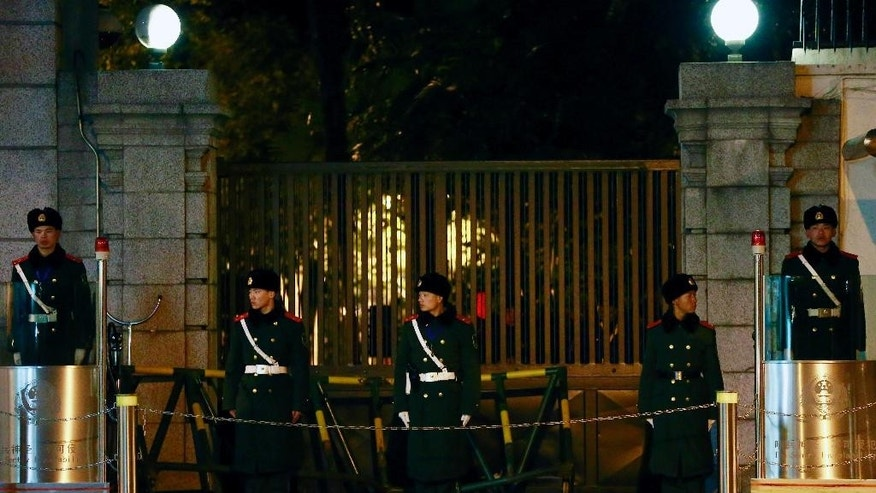 In this Thursday, Feb. 12, 2015 photo, Chinese paramilitary policemen stand guard near a damaged barrier placed at the entrance gate of the U.S. Consulate in Shanghai, China. A Chinese man, identified as 35-year-old Liu Daojie, rammed his car into the barrier and injured an armed police officer, officials said Friday, Feb. 13. (AP Photo) CHINA OUT