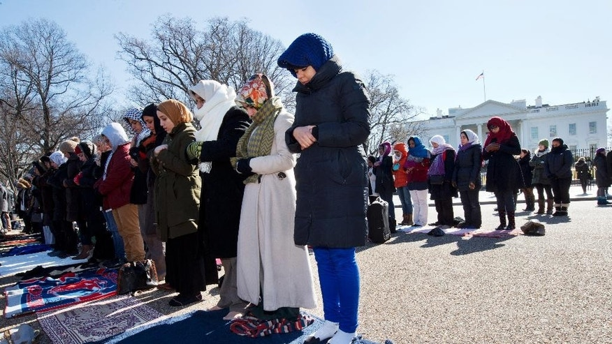 "Fatima Chrifi, a teacher at Georgetown University, center, prays with a group of Muslims and their supporters during Friday prayers outside the White House in Washington, Friday, Feb. 13, 2015, in the wake of the murder of three young North Carolina Muslims. The gathering was in memory of the Chapel Hill shooting victims, and to press federal authorities for a hate crime investigation.? ""I'm here to denounce hate and violence,"" says Chrifi, ""and to bring awareness to this issue."" (AP Photo/Jacquelyn Martin)"