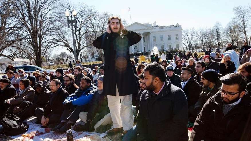 A student from Georgetown University, who asked not to be named, sings the call to prayer as a group of Muslim people and their supporters prepare to say the Friday prayers outside the White House in Washington, Friday, Feb. 13, 2015, in the wake of the murder of three young North Carolina Muslims. The gathering was in memory of the Chapel Hill shooting victims, and to press federal authorities for a hate crime investigation.? (AP Photo/Jacquelyn Martin)