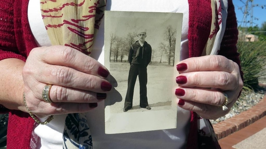 Penny Welch, of Illinois, holds a picture of her father, World War II veteran LeRoy James Vacovsky on Friday, Feb. 13, 2015 in Tucson, Ariz. Vacovsky's  Navy uniform found in the home of former Rep. Gabby Giffords of Arizona and her husband Mark Kelly. Welch and her husband, David, traveled to Tucson to pick up the uniform after Kelly tracked them down. Giffords' mother bought her the uniform when she married Kelly several years ago. (AP Photo/Astrid Galvan)