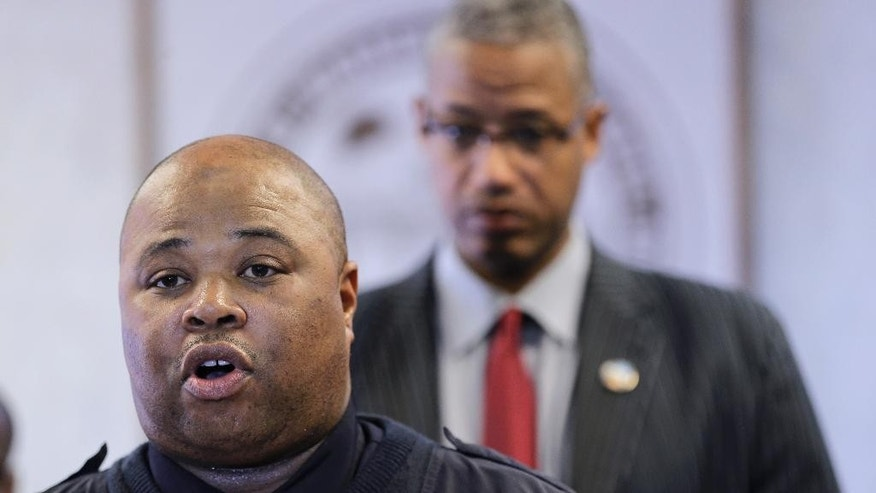 Warrensville Heights Police Chief Wesley Haynes, left, answers questions during a news conference Friday, Feb. 13, 2015, in Warrensville Heights, Ohio. Police officers and government agents surrounded a house in Cleveland early Friday and arrested  Douglas Shine Jr., a man they suspect killed three people and injured three others in a suburban barbershop shooting last week, officials said.   (AP Photo/Tony Dejak)