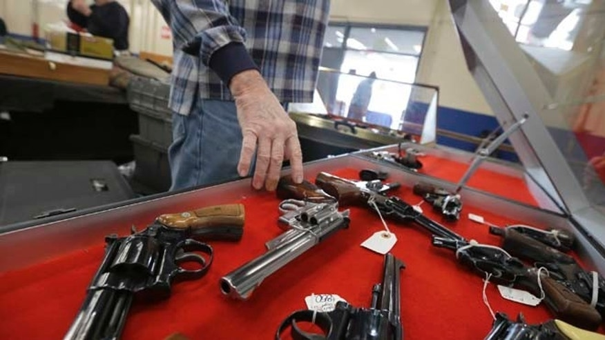 Feb. 6, 2015: Gun salesman arranges handguns in a display case in advance of a show at the Arkansas State Fairgrounds in Little Rock, Ark.