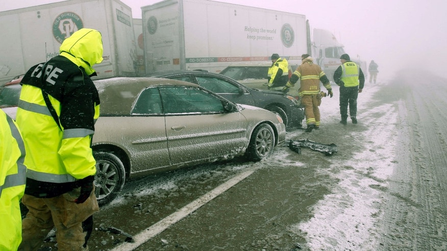 FEb. 14, 2015: First responders check on occupants of a multi-vehicle accident in near white out conditions, blocks west bound I-70.