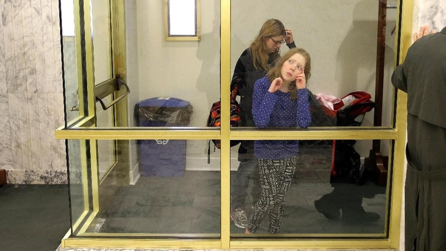 Christine Hartman, left, of Arlington, Wash., waits outside a House hearing room with her daughter Natalie, 12, during a hearing for House Bill 2009 at the Capitol in Olympia, Wash., Tuesday, Feb. 17, 2015. Hartman believes her daughter, who is developmentally delayed and faces multiple health challenges, was adversely affected by vaccines the child received as a baby, and was waiting to testify against the bill, which would remove personal or philosophical opposition as an acceptable reason for parents to not vaccinate their school-age children. Currently, Washington allows school vaccination exemptions for medical, religious and personal or philosophical beliefs. (AP Photo/Ted S. Warren)