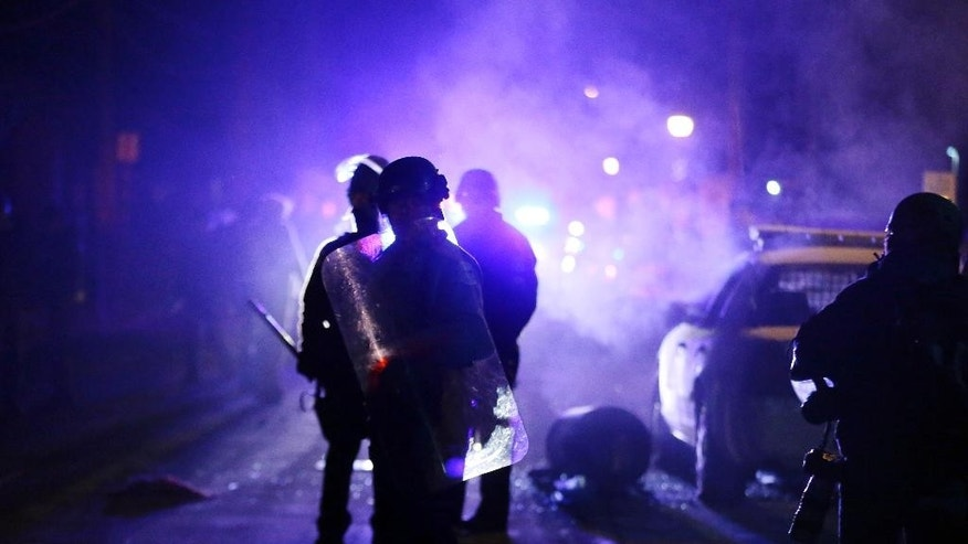 FILE - In this Nov. 25, 2014 file photo, police officers watch protesters as smoke fills the streets in Ferguson, Mo. after a grand jury's decision in the fatal shooting of Michael Brown. Newly released documents reveal that police planning for a grand jury announcement wanted Guard troops and armored Humvees stationed in the Ferguson neighborhood where Brown had been shot. But the records show the requests were not granted, because Missouri Gov. Jay Nixon preferred to use the Guard in a support role to police. (AP Photo/Charlie Riedel, File)