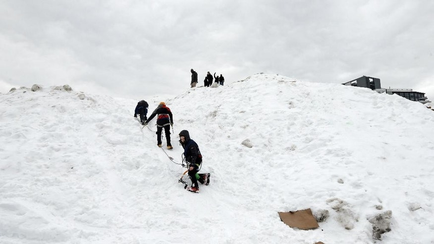 "Three students from the Massachusetts Institute of Technology jokingly use mountaineering gear to make their way down from a massive snow pile on the MIT campus in Cambridge, Mass., Wednesday, Feb. 18, 2015. The mountain of excess snow has been dubbed the ""Alps of MIT"" and is being used for climbing, sledding and posing. (AP Photo/Elise Amendola)"