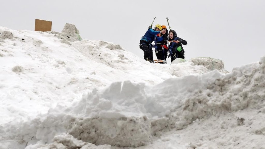 "Three students from the Massachusetts Institute of Technology take a selfie after jokingly using mountaineering gear to make their way up a massive snow pile on the MIT campus in Cambridge, Mass., Wednesday, Feb. 18, 2015. The mountain of excess snow has been dubbed the ""Alps of MIT"" and is being used for climbing, sledding and posing. (AP Photo/Elise Amendola)"