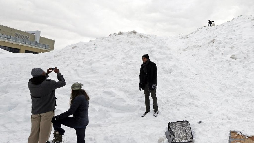 "Workers on lunch break from a nearby business take photos of a massive snow pile on the Massachusetts Institute of Technology campus in Cambridge, Mass., Wednesday, Feb. 18, 2015. The mountain of excess snow has been dubbed the ""Alps of MIT"" and is being used for climbing, sledding and posing. (AP Photo/Elise Amendola)"