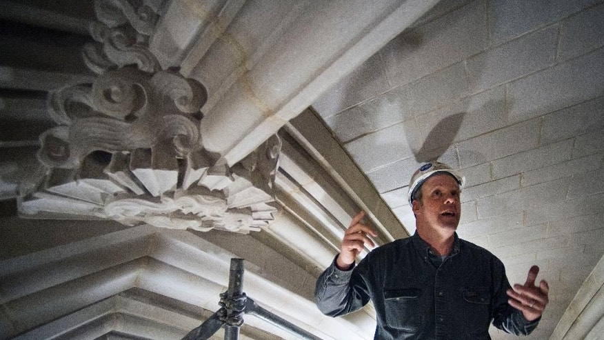 Head Mason Joe Alonso stands next to a boss stone in the ceiling 100 feet above the nave floor of the Washington National Cathedral in Washington, Wednesday, Feb. 18, 2015, as he talks about repairs and cleaning of the stonework at cathedral, The Washington National Cathedral has finished the first phase of restoration work needed after an earthquake in 2011. The iconic Episcopal cathedral in northwest Washington is holding a news conference Wednesday to discuss details of the restoration work, estimated to cost $32 million overall. Additional restoration work is expected to take years. (AP Photo/Cliff Owen)
