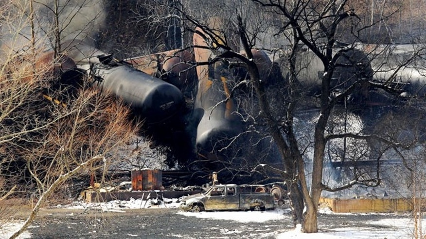 Feb. 17, 2015: Train cars remain on the scene following a train derailment near Mount Carbon, W.Va. A CSX train carrying more than 100 tankers of crude oil derailed Monday in a snowstorm, sending a fireball into the sky and threatening the water supply of nearby residents, authorities and residents said Tuesday. (AP Photo/The Register-Herald, Chris Jackson)