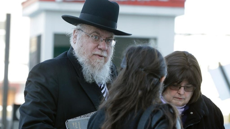 Rabbi Mendel Epstein, left, arrives for his trial at federal court in Trenton, N.J. on Wednesday, Feb. 18, 2015. Prosecutors say Epstein employed a kidnap team to force unwilling Jewish husbands to divorce their wives. (AP Photo/Mel Evans)