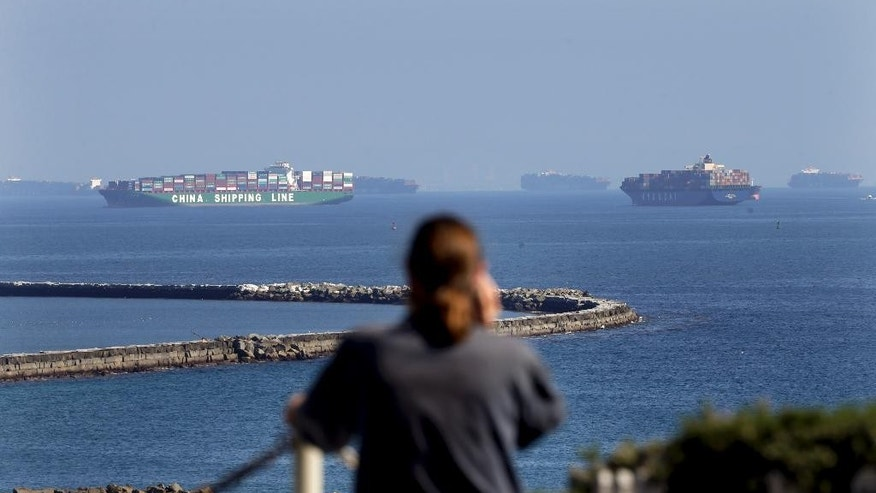 A man in foreground talks on the phone Tuesday, Feb. 17, 2015, in the San Pedro section of Los Angeles as cargo ships are anchored near the Ports of Long Beach and Los Angeles. Seaports in the U.S. West Coast that were all but shut over the weekend because of a contract dispute are reopening as the nation's top labor official tries to solve a stalemate between dockworkers and their employers that already has disrupted billions of dollars in U.S. international trade. (AP Photo/Jae C. Hong)