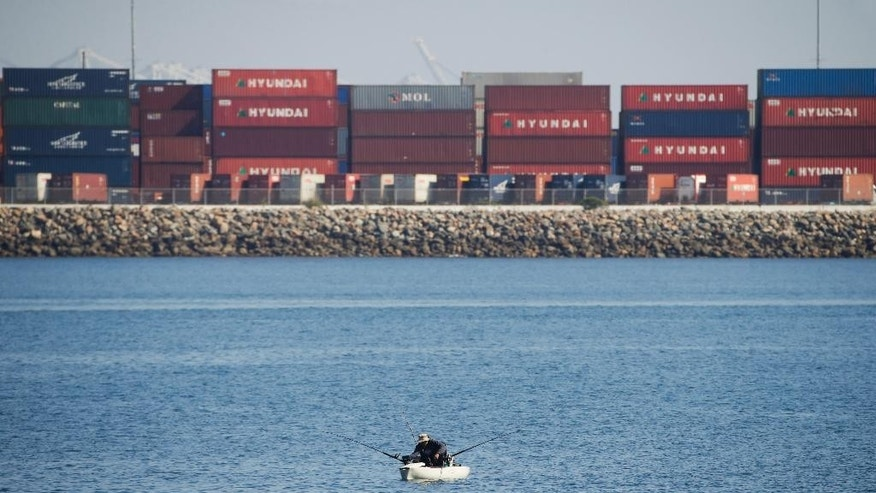 A man fishes near Cabrillo Beach, Tuesday, Feb. 17, 2015, in the San Pedro section of Los Angeles as shipping containers are stacked up at the Port of Los Angeles.  Seaports in the U.S. West Coast that were all but shut over the weekend because of a contract dispute are reopening as the nation's top labor official tries to solve a stalemate between dockworkers and their employers that already has disrupted billions of dollars in U.S. international trade. (AP Photo/Jae C. Hong)