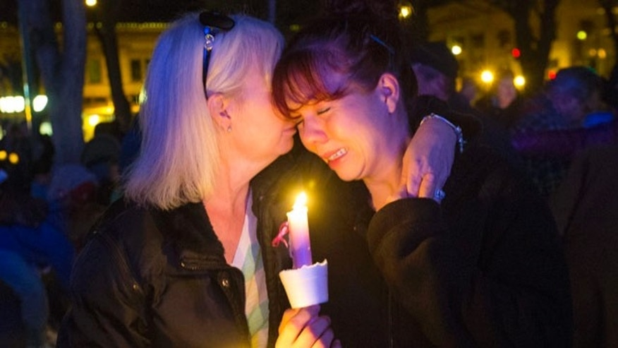 Feb. 18, 2015: Tonya Castillo, left, comforts her daughter Tiffany Reid during a candlelight memorial for Kayla Mueller in Prescott, Ariz. (AP Photo/The Arizona Republic, Michael Chow)