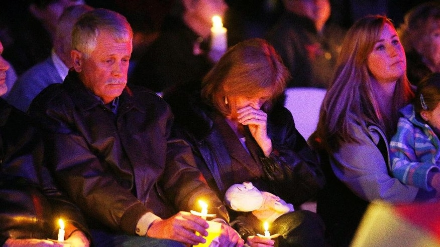 Carl, left, and Marsha Mueller, center, hold candles at the memorial in honor of their daughter Kayla Mueller on Wednesday, Feb. 18, 2015, in Prescott, Ariz. Kayla Mueller's death earlier this month was confirmed by her family and U.S. officials. The 26-year-old international aid worker from Prescott had been captured in Syria in August 2013. (AP Photo/The Arizona Republic, Rob Schumacher)