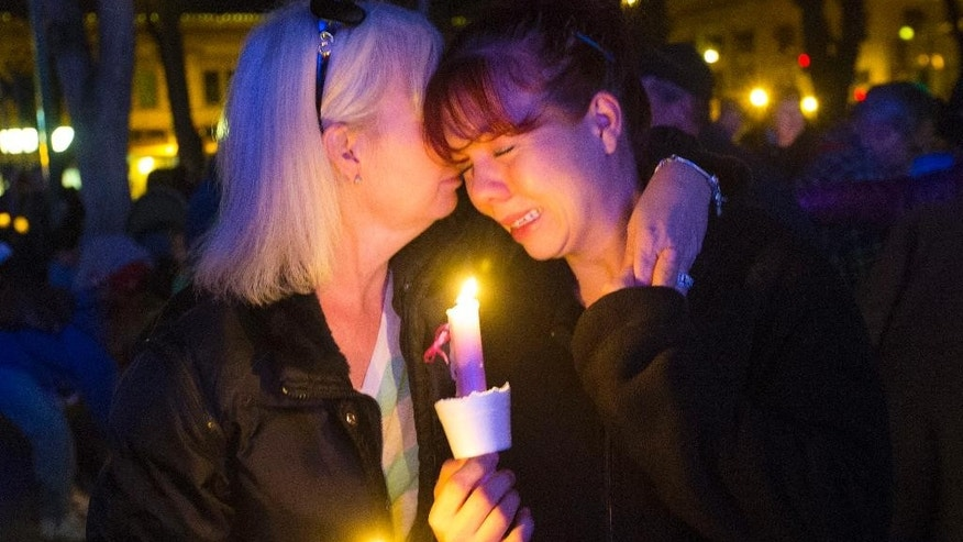 Tonya Castillo, left, comforts her daughter Tiffany Reid during a candlelight memorial for Kayla Mueller in Prescott, Ariz., Wednesday, Feb. 18, 2015. Kayla Mueller's death earlier this month was confirmed by her family and U.S. officials. The 26-year-old international aid worker from Prescott had been captured in Syria in August 2013. (AP Photo/The Arizona Republic, Michael Chow)