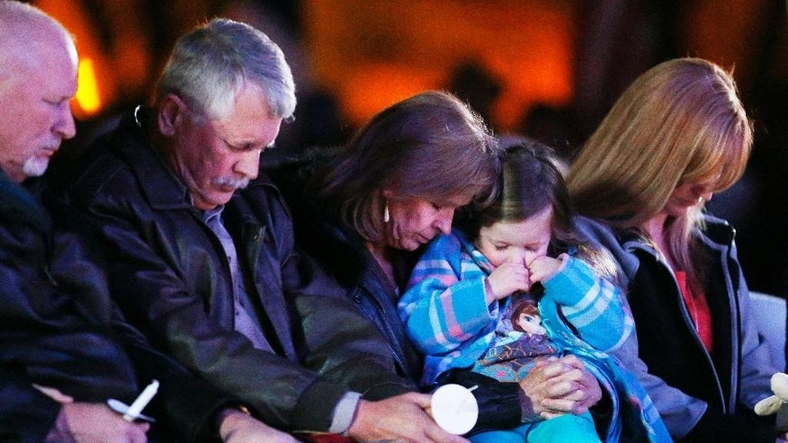 Carl, second from left, and Marsha Mueller, center, bow in prayer at the candlelight memorial in honor of their daughter Kayla Mueller on Wednesday, Feb. 18, 2015, in Prescott, Ariz. Kayla Mueller's death earlier this month was confirmed by her family and U.S. officials. The 26-year-old international aid worker from Prescott had been captured in Syria in August 2013. (AP Photo/The Arizona Republic, Rob Schumacher)