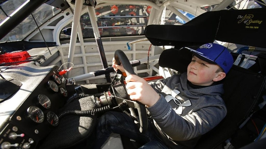 """Landon Neu, 8, of Jacksonville, Fla., experiences what it's like to be behind the wheel of a race car at the NASCAR Acceleration Nation interactive display at Daytona International Speedway, Thursday, Feb. 19, 2015, in Daytona Beach, Fla. Students who like NASCAR take note: You need a lot of geometry and physics to get a race car to go 200 laps at speeds that can top 200 mph. In a nod to the often overlooked science behind races like Sunday's Daytona 500, NASCAR is announcing a yearslong commitment to promote """"STEM"""" in classrooms. STEM is the buzzword for science, technology, engineering and math. (AP Photo/John Raoux)"""