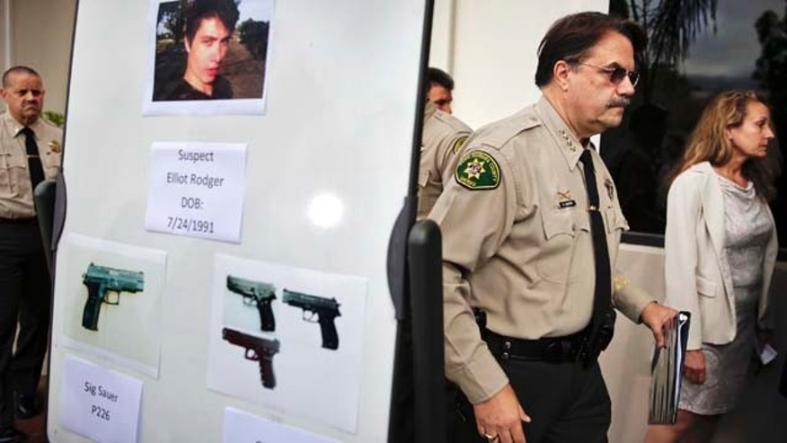 FILE- In this May 24, 2014, file photo, Santa Barbara County Sheriff Bill Brown, right, walks past a board showing the photos of gunman Elliot Rodger and the weapons he used in the mass shooting that took place in Isla Vista, Calif. (AP Photo/Jae C. Hong,File)