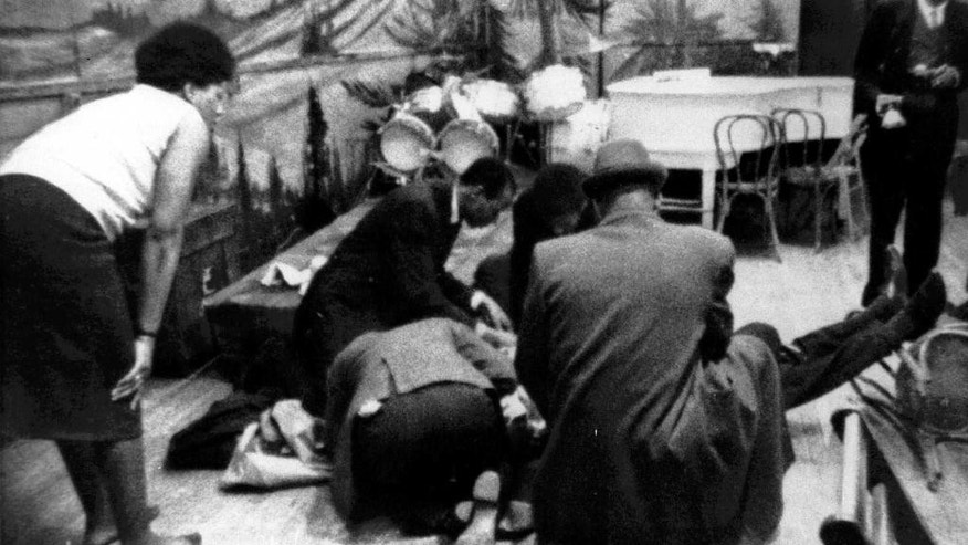 FILE- In this Feb. 21, 1965 file photo, Human rights activist Malcolm X is tended to as he lies mortally wounded on the stage of the Audubon ballroom in the Harlem section of New York after being shot multiple times. On Saturday, Feb. 21, 2015, the Malcolm X and R. Betty Shabazz Memorial and Educational Center will hold a ceremony to recognize the 50th commemoration of the assassination. (AP Photo/WCBS-TV)