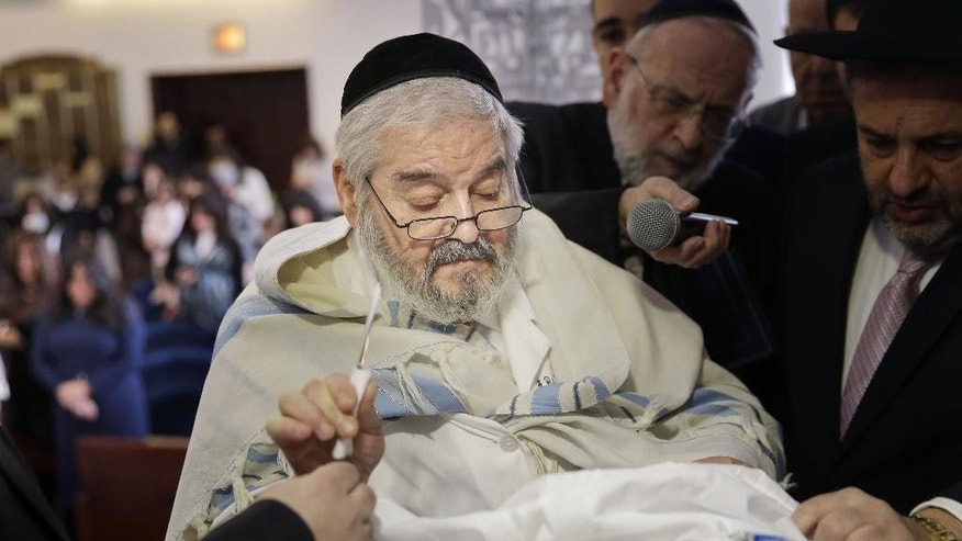 In this Feb. 11, 2015 photo, Abraham Romi Cohn is handed a scalpel during the bris, or ritual circumcision, of Yosef Sananas in New York. Mayor Bill de Blasio's administration is negotiating a medical protocol that would allow for religious freedom as it navigates health officials' concern over the practice of oral suction during ultra-Orthodox circumcision ceremonies, in which a rabbi sucks blood from a wound on the penis. (AP Photo/Seth Wenig)