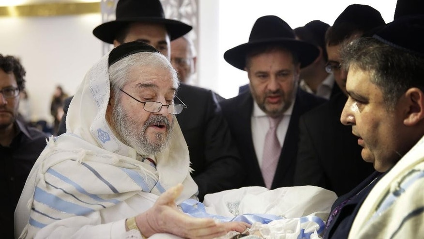 In this Feb. 11, 2015 photo, Abraham Romi Cohn, left, performs the bris, or ritual circumcision, of Yosef Sananas in New York. Mayor Bill de Blasio's administration is negotiating a medical protocol that would allow for religious freedom as it navigates health officials' concern over the practice of oral suction during ultra-Orthodox circumcision ceremonies, in which a rabbi sucks blood from a wound on the penis. (AP Photo/Seth Wenig)