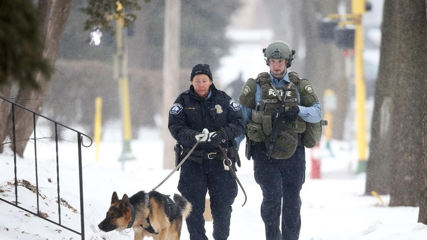An officer searches with a dog accompanied by a SWAT team member after a Minneapolis police officer was shot , Saturday, Feb. 21, 2015, in Minneapolis.  Police say two officers were standing by their marked squad car after having handling a burglary call early in the day when someone shot one of them. The wounded officer's partner drove him to a hospital, where he's listed in satisfactory. No one is in custody. (AP Photo/Star Tribune, David Joles)  MANDATORY CREDIT; ST. PAUL PIONEER PRESS OUT; MAGS OUT; TWIN CITIES LOCAL TELEVISION OUT