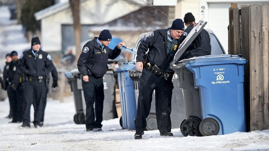 Minneapolis police officers search garbage and recycling bins in an alley after a Minneapolis police officer was shot , Saturday, Feb. 21, 2015, in Minneapolis.  Police say two officers were standing by their marked squad car after having handling a burglary call early in the day when someone shot one of them. The wounded officer's partner drove him to a hospital, where he's listed in satisfactory. No one is in custody. (AP Photo/Star Tribune, David Joles)  MANDATORY CREDIT; ST. PAUL PIONEER PRESS OUT; MAGS OUT; TWIN CITIES LOCAL TELEVISION OUT