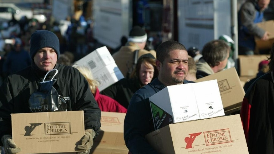 FILE - In this Feb. 19, 2009 file photo, Residents of Wilmington, Ohio carry free boxes of food and personal care products provided by the relief organization Feed the Children. As what would become the Great Recession was pounding the country, thousands of workers were left jobless with the departure of express carrier, DHL, from the Wilmington Air Park. Ohio governor John Kasich will spotlight the slowly rebounding city by delivering his State of the State address there Feb. 24, 2015. (AP Photo/Skip Peterson)