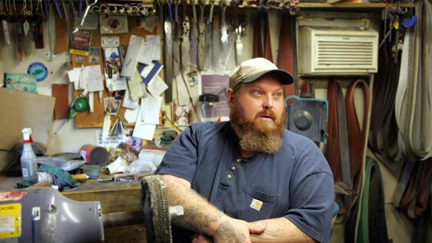 FILE - In this In this Aug. 28, 2009, file photo, Michael O'Machearley talks about the economy in his workshop in Wilmington, Ohio. O'Machearley, a former employee of ABX Air, was now making custom knives for his living, 15 months since air cargo shipper DHL Express announced it was pulling out of this southwest Ohio city, a move that resulted in the layoff of thousands of employees. (AP Photo/Skip Peterson, File)