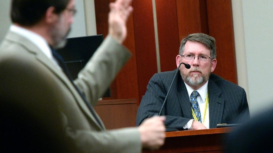 Defense lawyer Fred Metos, left, questions medical examiner Dr. Erik Christensen, during the trial of John Brickman Wall in Salt Lake City on Monday, Feb. 23, 2015. Christensen said that an autopsy showed that von Schwedler had suspicious wounds on her wrist and leg. Christensen said Monday that the 2011 death of Uta von Schwedler in Salt Lake City initially looked like a suicide, but the wounds pointed to a homicide. (AP Photo/The Salt Lake Tribune, Al Hartmann, Pool)