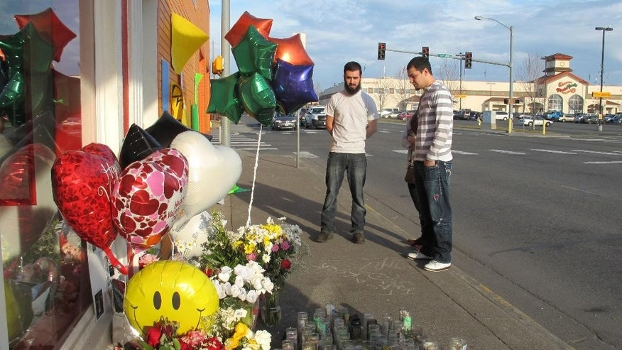 In this Feb. 18, 2015 photo, pedestrians view a memorial in Pasco, Wash., on the sidewalk where Antonio Zambrano-Montes, an unarmed man who was running away from police at a crowded intersection, fell after being fatally shot by police. (AP Photo/Nicholas K. Geranios)
