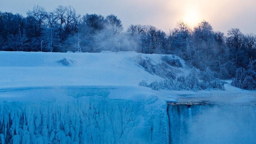 The sun rises over masses of ice formed around the Canadian 'Horseshoe' Falls in Niagara Falls, Ontario, Canada, Thursday, Feb. 19, 2015. (AP Photo/The Canadian Press,Aaron Lynett)