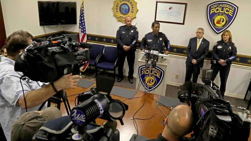 Fort Lauderdale Police Chief Frank Adderly, center, addresses the media about a Fort Lauderdale police officer who pushed and slapped a man during an arrest after a video surfaced showing the incident, Tuesday, Feb. 24, 2015, in Fort Lauderdale, Fla.  A criminal investigation has been launched against a police officer who was videotaped pushing and slapping a homeless man at a downtown bus terminal, officials said Tuesday.  (AP Photo/South Florida Sun-Sentinel, Susan Stocker )  MAGS OUT