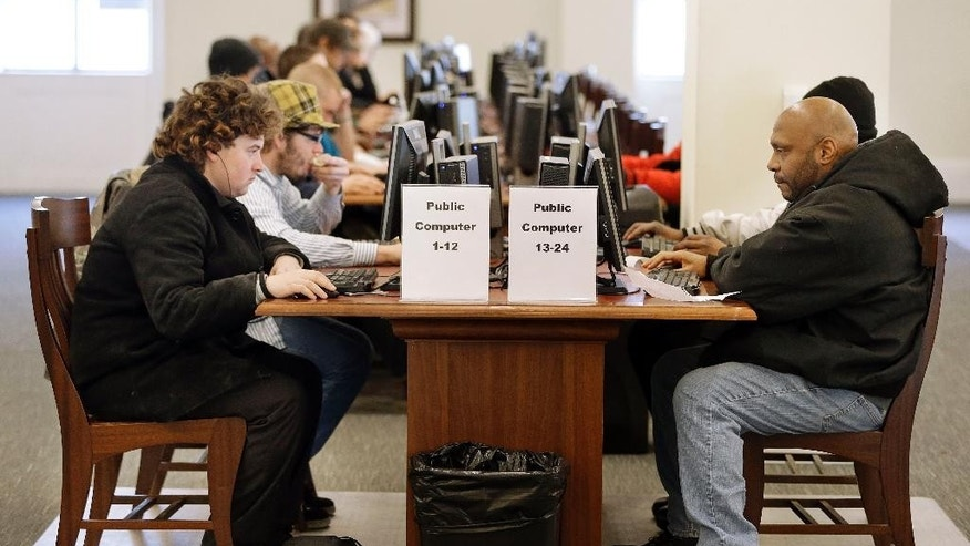 In this Feb. 19, 2015 photo, Larry Lawrence, left, who slept on the street the night before, works at a computer at the Nashville Public Library in Nashville, Tenn. As cuts to social services and mental health programs continue to drive the homeless and disadvantaged to use libraries as day shelters, some libraries are beginning to view services for that population as an important part of their mission. (AP Photo/Mark Humphrey)