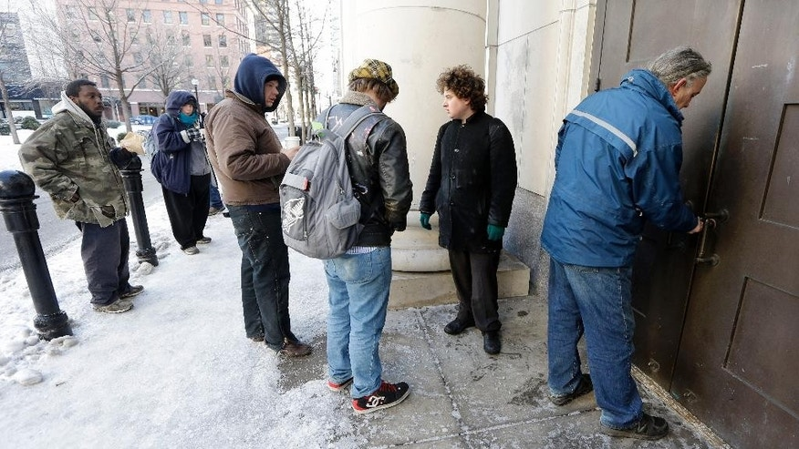 In this Feb. 19, 2015 photo, people wait to enter the Nashville Public Library as Rick Reed, right, the library's superintendent of plant operations and maintenance, unlocks the front doors in Nashville, Tenn. Many public libraries discourage homeless people from hanging around. But more and more libraries are beginning to view services to the homeless as an important part of their mission. (AP Photo/Mark Humphrey)