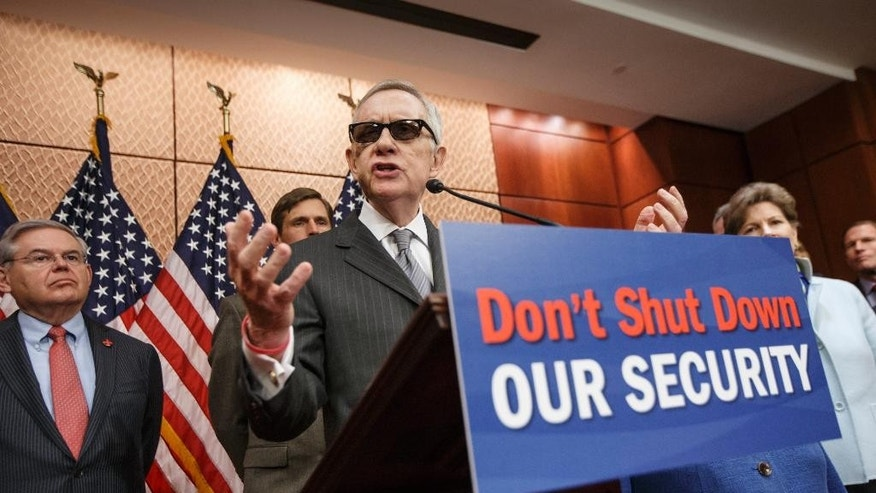 "The Senate Democratic Caucus, led by Senate Minority Leader Harry Reid of Nev., center, gestures during a news conference on Capitol Hill, Tuesday, Feb. 24, 2015, to urge Republicans to support a ""clean bill"" to fund the Homeland Security Department as that agency's budget expires later this week. The DHS budget is at a standstill over provisions attached to a Homeland Security spending bill aimed at blocking President Barack Obama's executive actions on immigration.  Sen. Bob Menendez, D-N.J. is at left. (AP Photo/J. Scott Applewhite)"