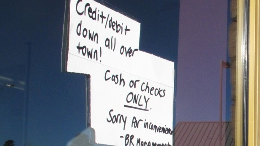 Feb. 25, 2015: A sign posted outside a Baskin-Robbins ice cream store in Flagstaff, Ariz., advises customers that only cash or checks will be accepted due to an Internet and phone outage. (AP Photo/Felicia Fonseca)
