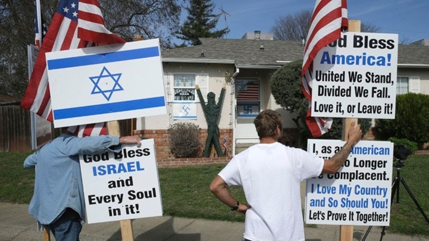 Feb. 26, 2015: Robert Dixon, left, and Kraig Smith, demonstrate outside a home calling for removal of swastikas displayed on the home in Sacramento, Calif.,  Thursday.