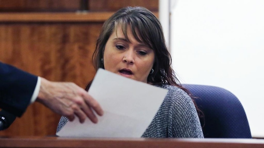Kelly Rose Belanger, the former bar manager at South Street Cafe in Providence, examines a copy of a receipt while testifying at the murder trial of former New England Patriots NFL football player Aaron Hernandez at Bristol County Superior Court in Fall River, Mass., Thursday, Feb. 26, 2015.  Hernandez is charged in the murder of Odin Lloyd in 2013.  According to Belanger, Hernandez spent the earlier part of the night drinking with a group at a bar in Rhode Island, and smoking marijuana outside, on the evening that Lloyd was murdered. (AP Photo/Charles Krupa, Pool)