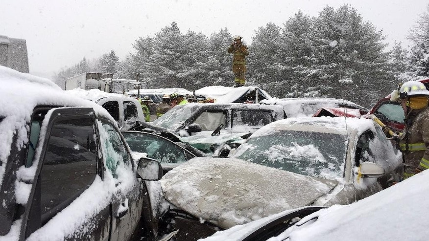 In this photo provided by Maine State Police and Maine Emergency Management, emergency personnel respond to a multi-vehicle pileup along Interstate 95 in Etna, Maine, about 20 miles west of Bangor, Wednesday, Feb. 25, 2015.  State police spokesman Steve McCausland said the pileup happened early Wednesday in heavy snow and involved many cars, a school bus and a semitrailer. No fatalities were immediately reported but McCausland said some of the injuries were serious.  (AP Photo/Maine State Police and Maine Emergency Management, Stephen McCausland)