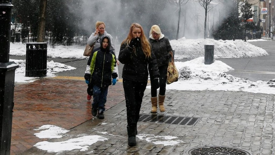 "Machine-generated fog wafts from ""A Winter Landscape Cradling Bits of Sparkle"" by artist Jennifer Wen Ma, as passers-by walk past the installation in Pittsburgh's Market Square on Thursday, Feb. 26, 2015. The Pittsburgh Post-Gazette says firefighters have been called to the location at least twice, including once Thursday morning, by people who mistook machine-generated fog that's part of a new art installation for smoke. (AP Photo/Keith Srakocic)"