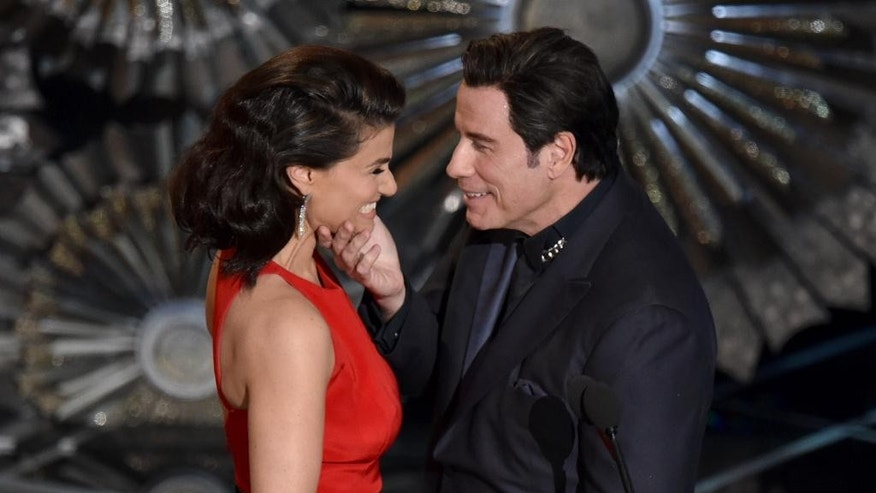 "FILE - In this Feb. 22, 2015 file photo, John Travolta, right, touches the face of Idina Menzel as they present the award for best original song at the Oscars at the Dolby Theatre in Los Angeles. Since strutting onto the big screen in ""Saturday Night Fever,"" John Travolta's career has been one of dramatic ups and downs, from comeback king to Internet meme. Travolta, 61, is prepping a handful of projects and ahead of the release of an explosive documentary on Scientology that focuses considerably on Travolta's relationship with the organization. (Photo by John Shearer/Invision/AP, File)"
