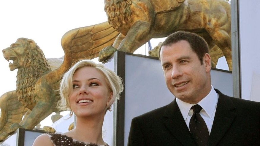 "FILE - In this Sept. 2, 2004 file photo, U.S. actor John Travolta, right, and actress Scarlett Johansson arrive to the presentation of the movie ""A Love Song For Bobby Long"" at the 61st edition of the Venice Film Festival in Venice, northern Italy. Since strutting onto the big screen in ""Saturday Night Fever,"" John Travolta's career has been one of dramatic ups and downs, from comeback king to Internet meme. Travolta, 61, is prepping a handful of projects and ahead of the release of an explosive documentary on Scientology that focuses considerably on Travolta's relationship with the organization.  (AP Photo/Domenico Stinellis, File)"
