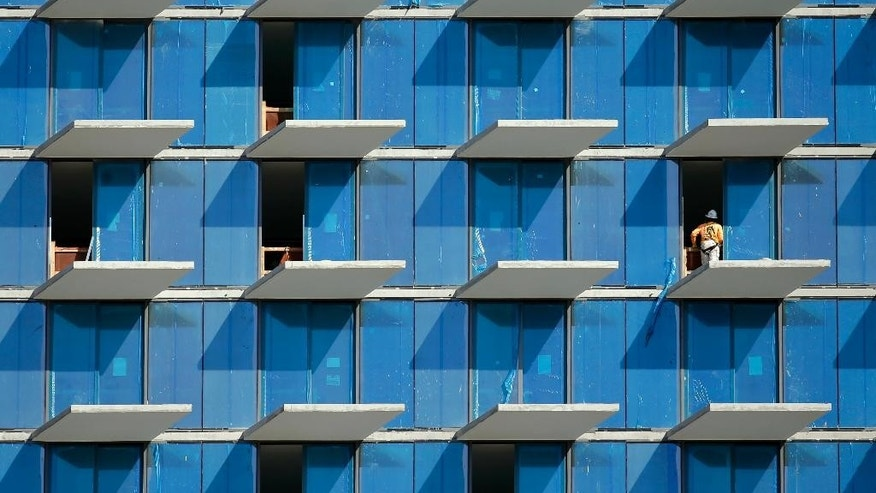 In this Tuesday, Feb. 3, 2015 photo, a construction worker stands on an outside balcony at Brickell City Centre, a $1.05 billion mixed-use development is located in Miami's financial district. The Commerce Department issues its second of three estimates of how fast the U.S. economy grew in the October-December quarter on Friday, Feb. 27, 2015. (AP Photo/Lynne Sladky)