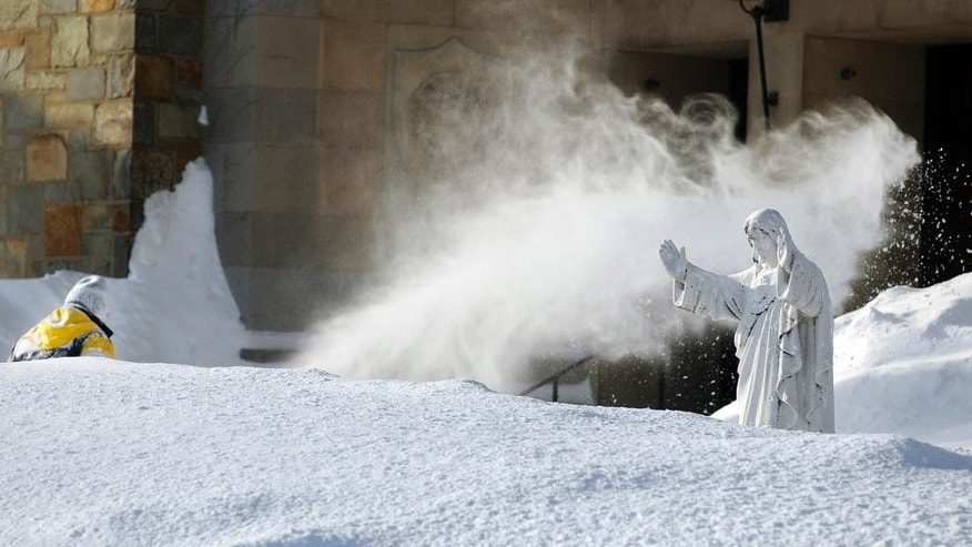 In this Monday, Feb. 16, 2015 photo, custodian George Blomquist clears snow from the grounds of Our Lady of the Angels Church after a weekend snowstorm in Worcester, Mass.  Churches, synagogues and mosques in New England report that attendance is down at worship services this winter, as many storms have hit over weekends. (AP Photo/Worcester Telegram & Gazette, Christine Peterson)