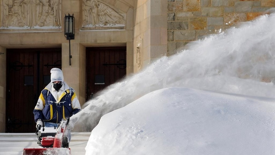 In this Monday, Feb. 16, 2015 photo, custodian George Blomquist clears snow from the sidewalk in front of Our Lady of the Angels Church after a weekend snowstorm in Worcester, Mass.  Churches, synagogues and mosques in New England report that attendance is down at worship services this winter, as many storms have hit over weekends. (AP Photo/Worcester Telegram & Gazette, Christine Peterson)