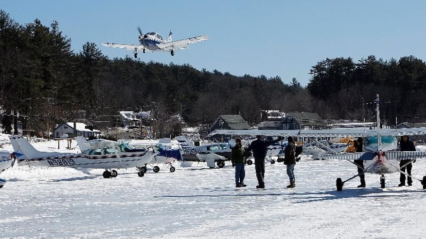 Planes fly into the ice runway on New Hampshire's Lake Winnipesaukee Saturday, Feb. 28, 2015, in Alton, N.H.  After weeks of weekend snowstorms pilots across the northeast got a chance to fly onto the only ice runway in the Lower 48 states approved by the Federal Aviation Administration. (AP Photo/Jim Cole)