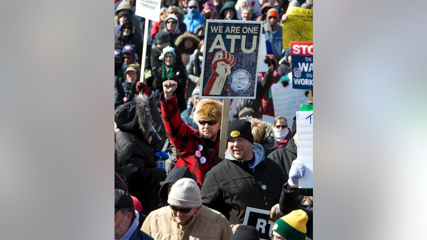 "Marc LeClair, of Wausau, Wis., center with sign, marches during a rally against a ""right-to-work"" proposal, on Saturday, Feb. 28, 2015, in Madison, Wis. Thousands of Wisconsin union workers rallied at the Capitol Saturday to protest a ""right-to-work"" proposal that would outlaw the mandatory payment of union dues, but the crowd was much smaller than those in 2011 against Gov. Scott Walker's law stripping public sector unions of much of their power.   (AP Photo/Wisconsin State Journal, Steve Apps)"