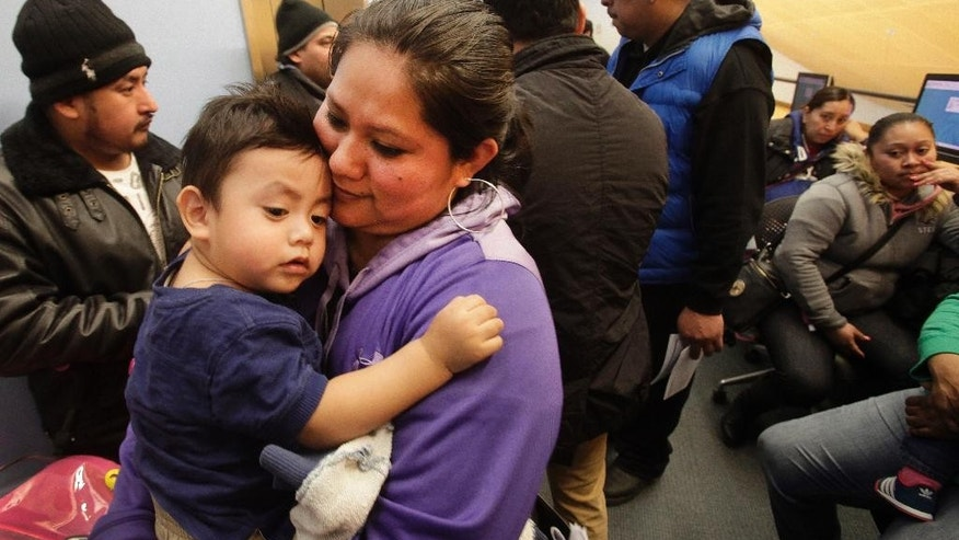 FILE - In this Jan. 12, 2015 file photo, Veronica Ramirez, originally from Mexico, holds her 15-month-old son, Lora, while waiting in line to apply for a municipal identification card on the first day they were available at the Bronx Library Center, in the Bronx borough of New York. A municipal ID program that city officials thought would draw a few hundred thousand people in its first year has been much more popular than anticipated, with New Yorkers waiting hours in line and months for appointments to register. City officials have scrambled to keep up with the demand.   (AP Photo/Mark Lennihan, File)